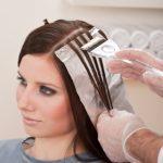 Professional hairdresser color female customer at design salon, creating highlights